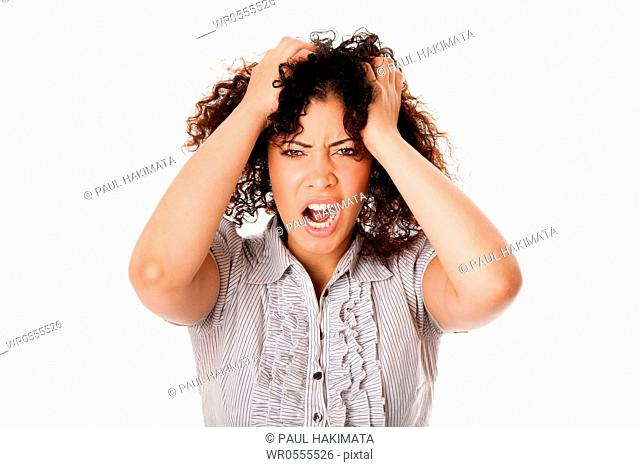 Frustrated angry formal corporate business woman with curly hairwith hands in hair and screaming yelling, isolated