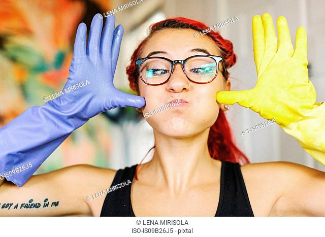 Portrait of young woman with pink hair pulling a face wearing mismatched rubber gloves