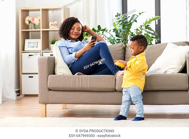 mother using smartphone and baby playing toy car