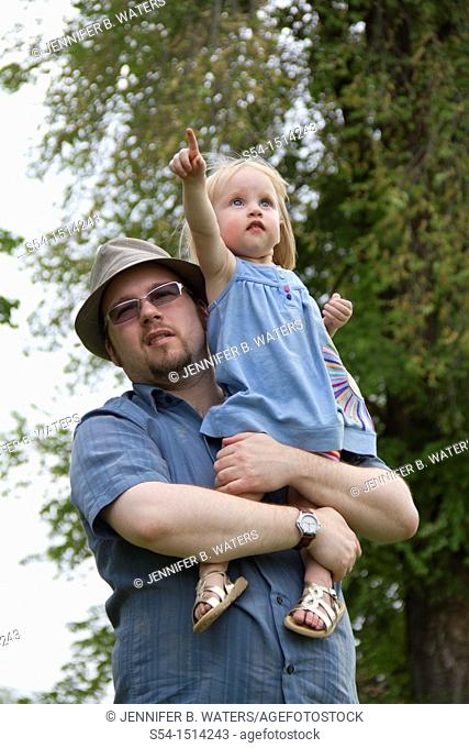 A man holding his young daughter at a park in Spokane, Washington, USA