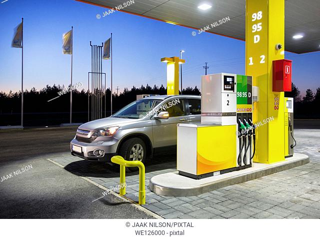 Car in gas station. Fuel, petrol dispenser and pillars. Fueling. Estonia. Twilight, lighted