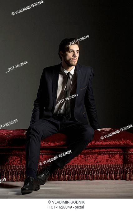 Full length thoughtful businessman sitting on ottoman against gray background