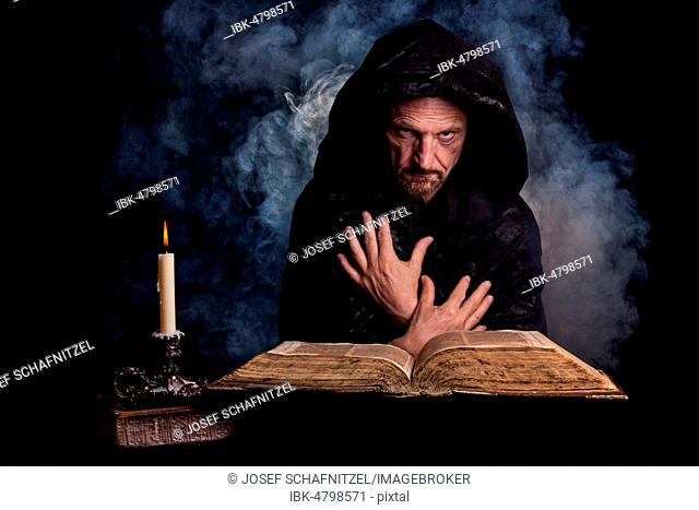 Man, with a black hooded coat, in front a burning candle and an old book, Germany