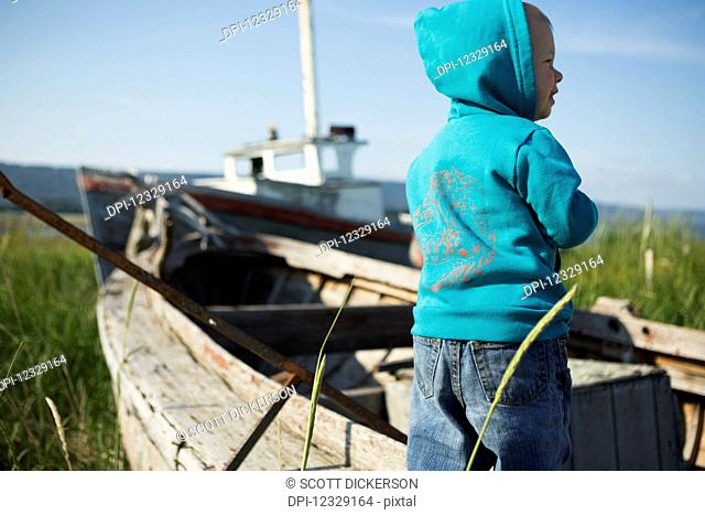 A Young Boy Stands Beside A Wooden Boat On The Grassy Shore Looking Out To The Water, Homer Spit; Homer, Alaska, United States Of America