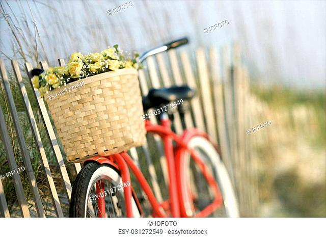 Red vintage bicycle with basket and flowers leaning against wooden fence at beach