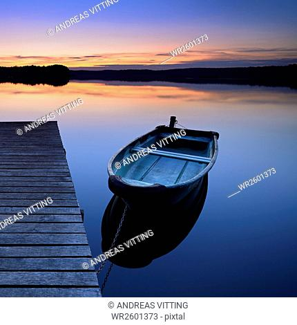 Footbridge with rowing boat at sunset, Grosser Lychensee, Uckermark district, Brandenburg, Germany