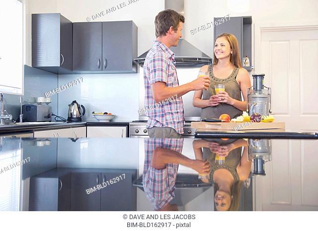 Caucasian couple drinking juice in kitchen