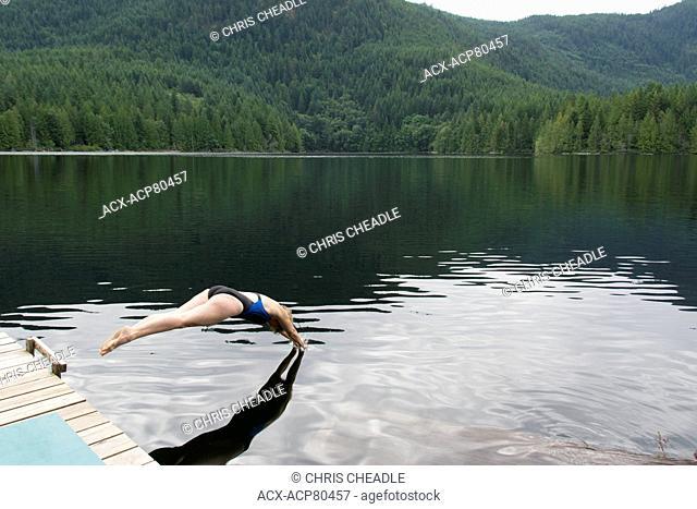 Woman dives in Klein Lake near Egmont, Sunshine Coast, British Columbia, Canada
