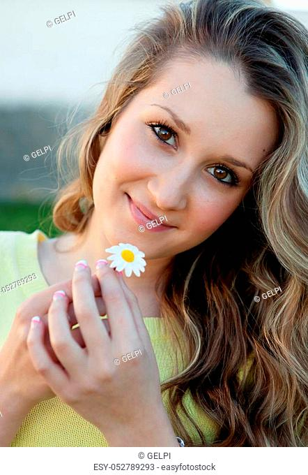 Nice blonde girl holding a daisy with face of love
