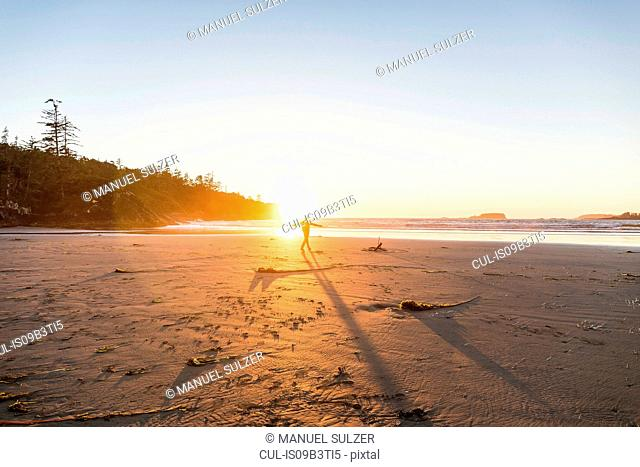 Man dancing on Long Beach at sunset, Pacific Rim National Park, Vancouver Island, British Columbia, Canada