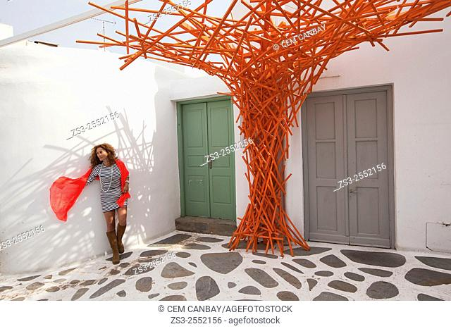 Woman posing with an orange scarf near a whitewashed house in town center, Mykonos, Cyclades Islands, Greek Islands, Greece, Europe