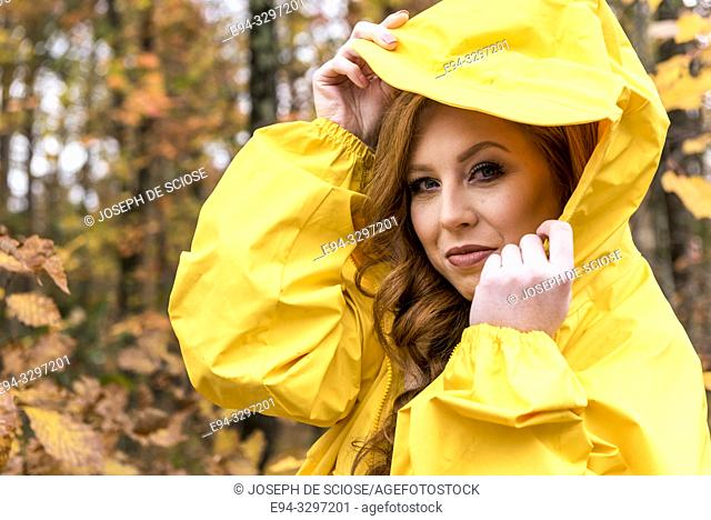 A 25 year old redheaded woman wearing a yellow jacket outdoors in the autumn
