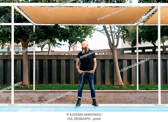 Mature male hipster standing below canopy with hands in pockets
