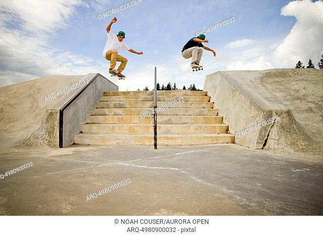 Two skateboarders simultaneously clear a 7-stair gap at the skatepark in Whitefish, Montana