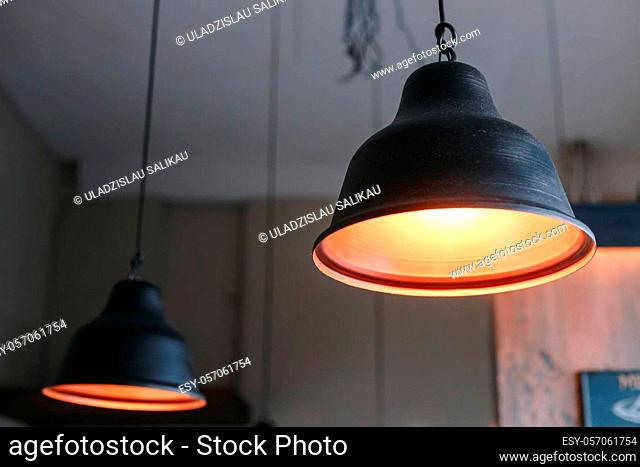 Black metal lamps hanging from the eiling grey wall interior