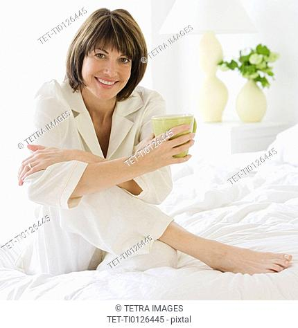 Woman sitting on bed holding coffee