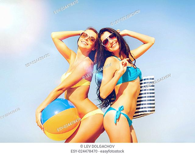 summer holidays, vacation and beach activities - girls with ball on the beach