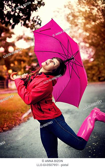 Cheerful woman with umbrella and rubber boots in the rain Debica, Poland