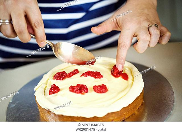 Close up high angle view of person wearing a blue and white stripy apron assembling a layer cake, holding spoon, placing raspberries on layer of cream
