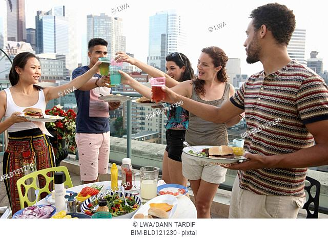 Friends enjoying barbecue on urban rooftop