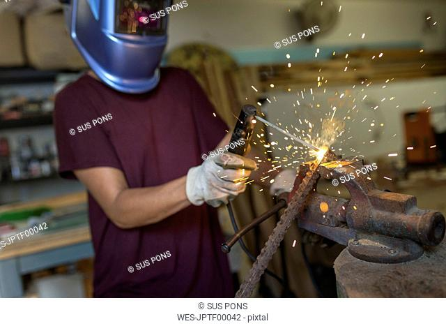 Craftswoman welding metal in her workshop