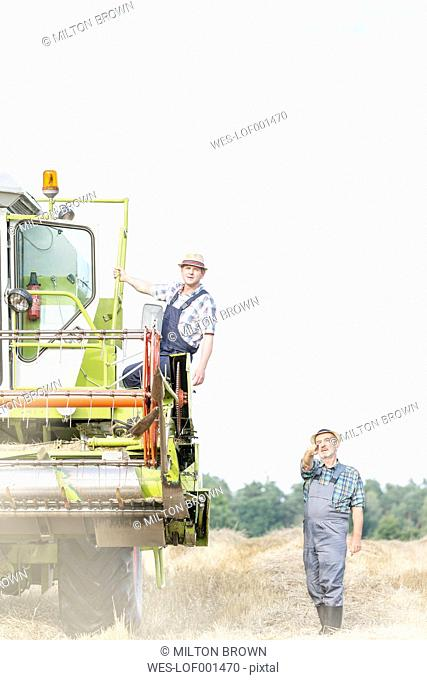 Two farmers with combine harvester on field