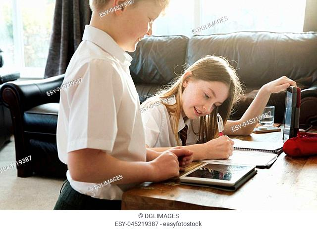 Little boy and his sister are studying together at home. They both have a digital tablet and the girl is writing in a planner