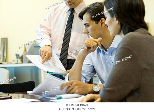 Executives looking at document together