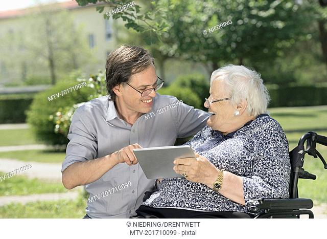 Son with disabled mother using digital tablet