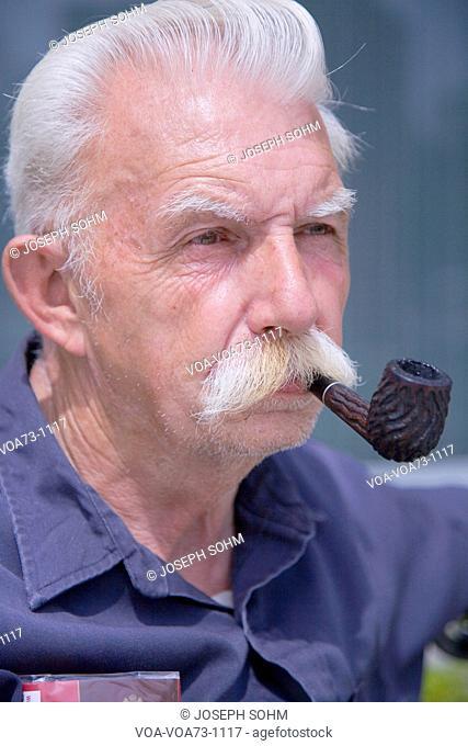 Male Senior Citizen smokes pipe, Quincy, Ma., USA