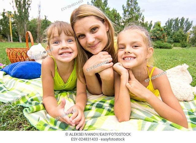 Mother and two girls lying on the grass on a picnic and fun look into the frame