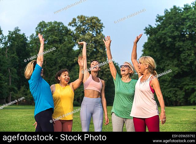 Multiethnic group of senior women training at park with fitness instructor - Active elderly people doing sport in the nature