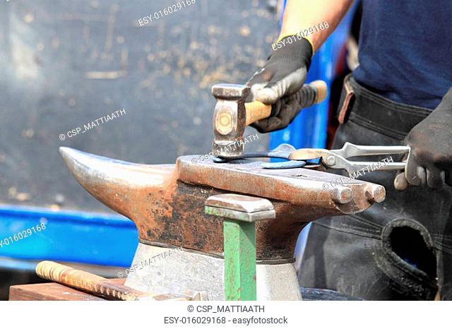 Farrier making a horseshoe
