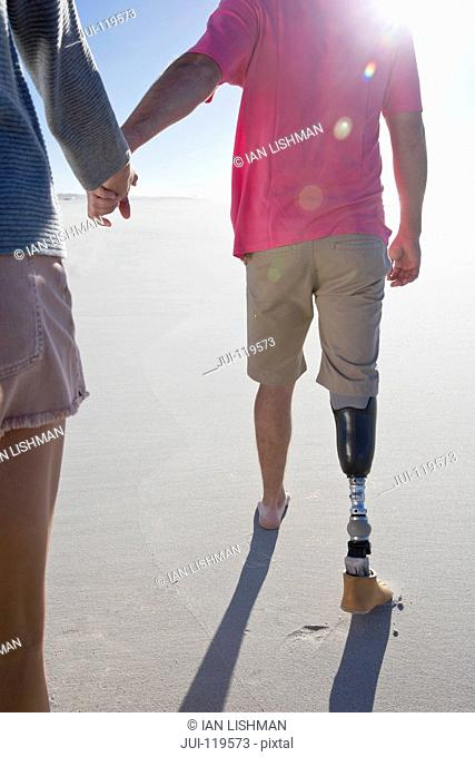 Close Up Shot Of Man With Artificial Leg Walking Along Beach Holding Hands With Female Partner On Summer Vacation