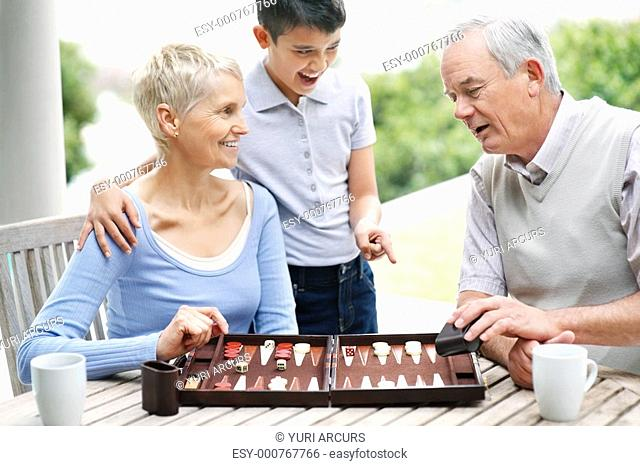 Happy boy watches senior man and woman play a game of backgammon