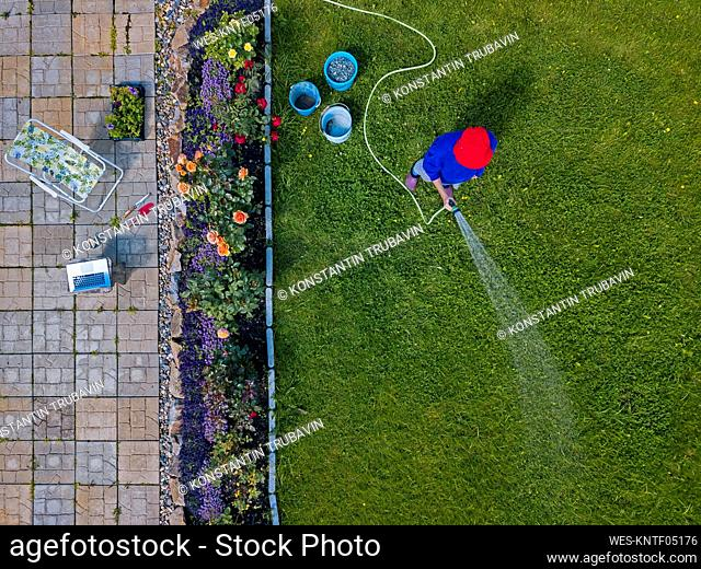 Aerial view of adult woman watering grass in backyard