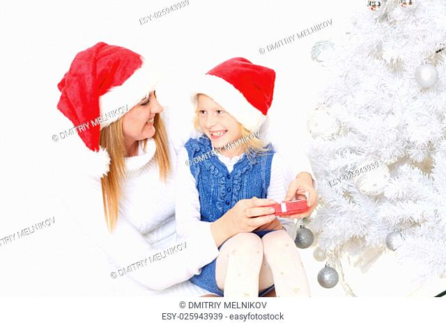 The pretty girl and her mother with gift box are sitting near Christmas tree on a white background