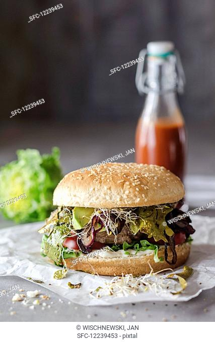A hamburger with seaweed bacon, bean sprouts and strawberry ketchup