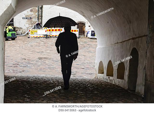 Turku, Finland A man with umbrella enters the main vaulted gate at the 13th century medieval Turku Castle