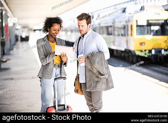 Young businessman and businesswoman using tablet together at the train station