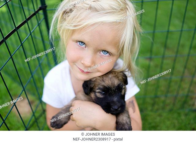 Portrait of girl holding puppy