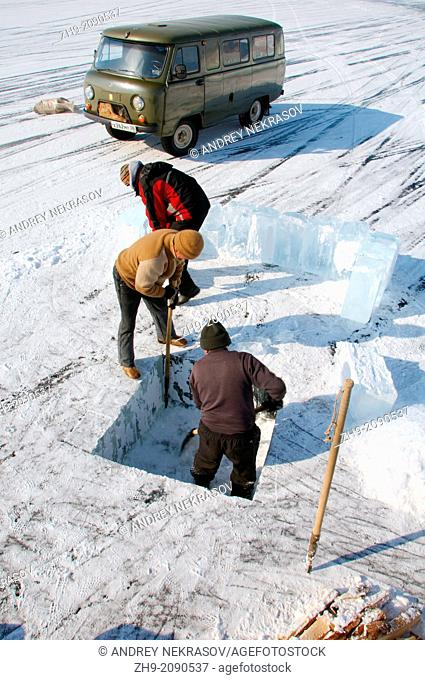 Man sawing an ice-hole for ice-diving, in Lake Baikal, Olkhon island, Siberia, Russia, Eurasia