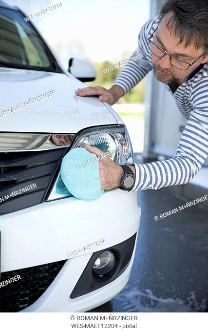 Man cleaning headlight of his car