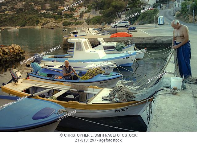 Old fishermen mending his nets in his small boat in the harbor at Punat on the Croatian island of Krk