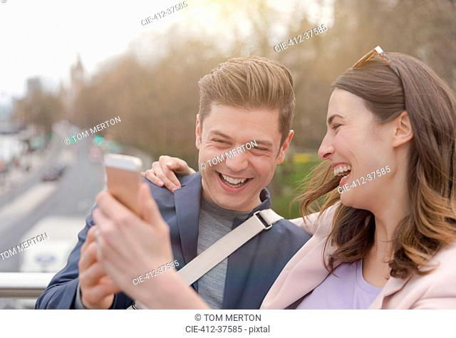 Laughing couple taking selfie with camera phone