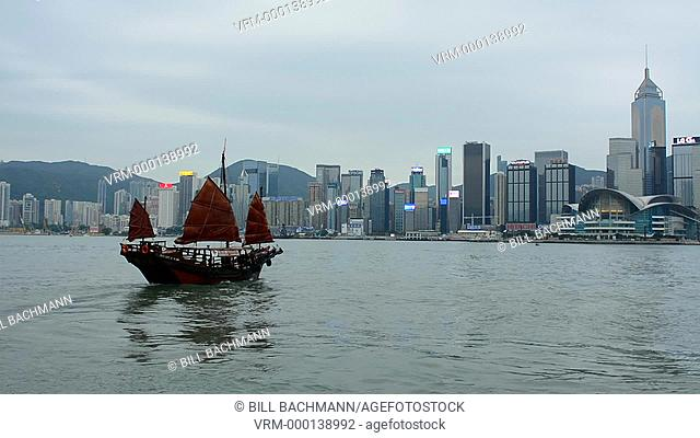 Hong Kong China skyline from water with traditional junk boat against city background