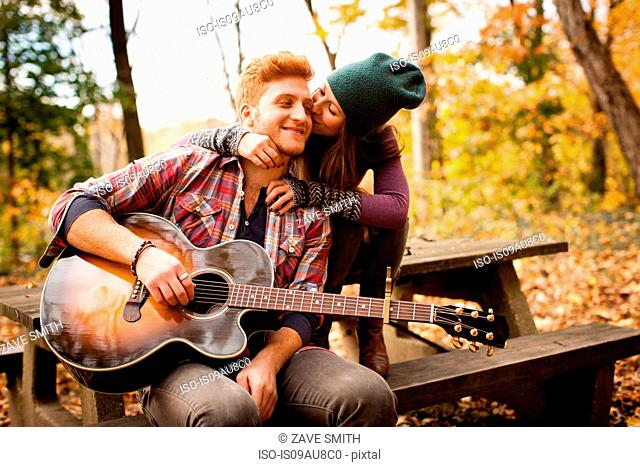 Romantic young couple playing guitar on picnic bench in autumn forest