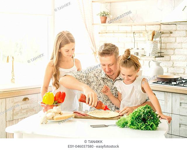 dad with two little daughters preparing pizza in the kitchen