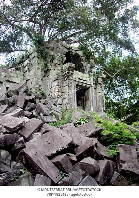 Beng Mealea temple with collapsed stone blocks and tree roots overtaking the building in Cambodia