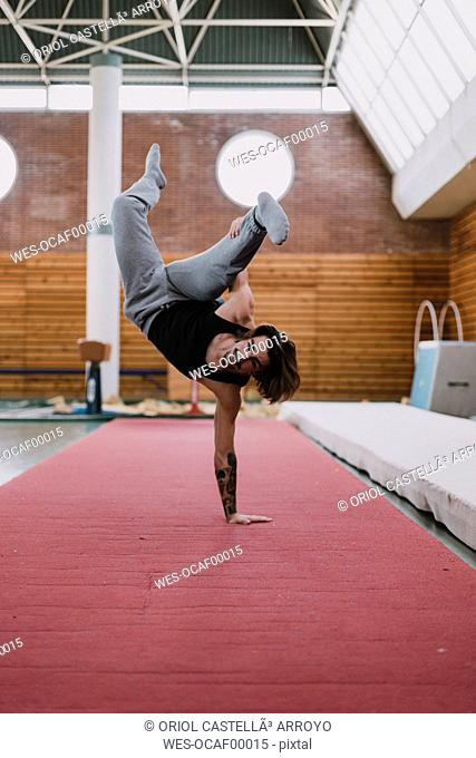 Young man doing acrobatic exercise in gym